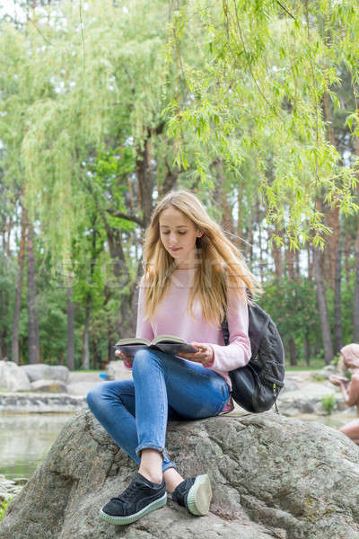Cute teenage-girl reading a book in the city park Stock photo © artsvitlyna