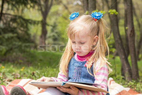 Cute little blonde girl with two ponytails relaxing with a book  Stock photo © artsvitlyna