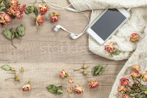 White knitting wool, dried roses flowers, mobile phone and headp Stock photo © artsvitlyna