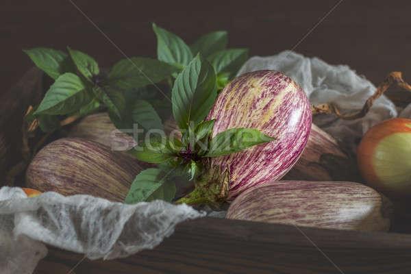 Purple graffiti eggplants, onion and green fresh basil in a wood Stock photo © artsvitlyna