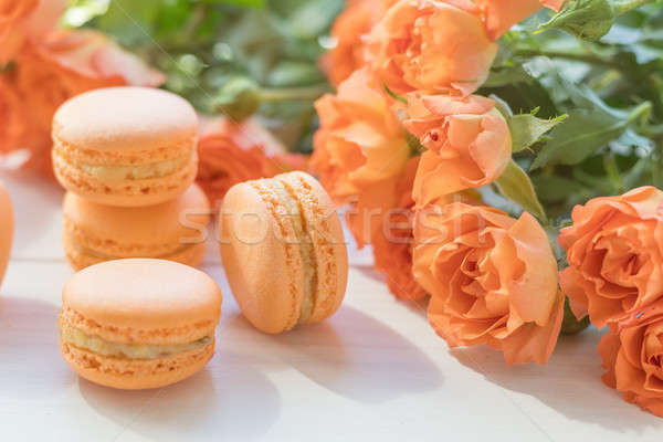 Stock photo: Orange macaroons and fresh little roses