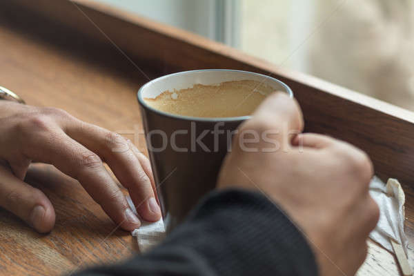 Cup of coffee in the hands of a man lying on a table in the cafe Stock photo © artsvitlyna