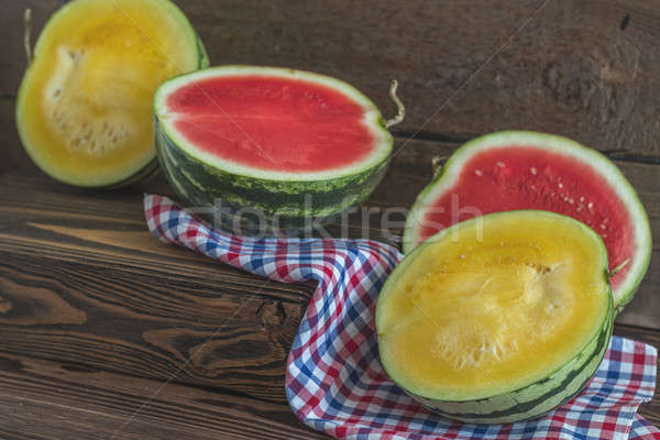 Stock photo: Cut red and yellow watermelons on a wooden box in a vintage wood