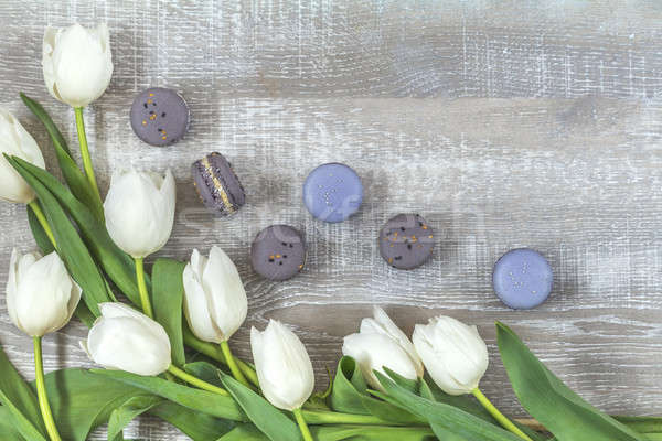 Stock photo: Many white tulips and gray macaroons on light wooden surface