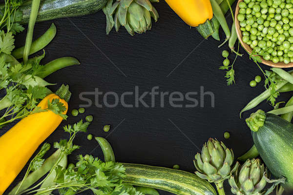 Fresh organic green vegetables on black stone floor Stock photo © artsvitlyna