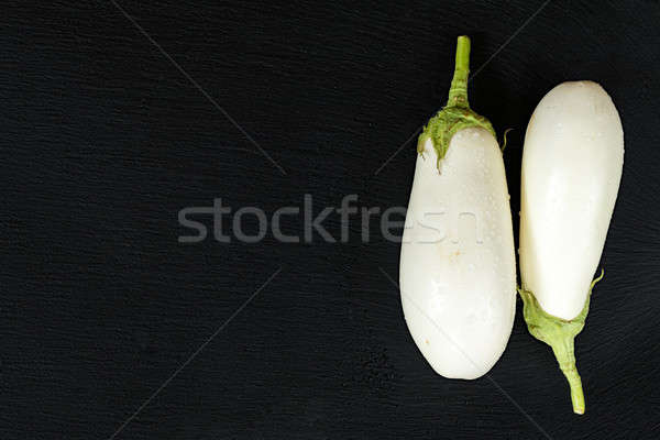 Stock photo: White eggplant on a black stone surface with water drops. Top vi