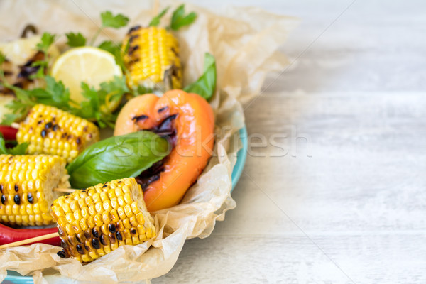 Corn baked in olive oil, with pepper, salt and basil on parchmen Stock photo © artsvitlyna