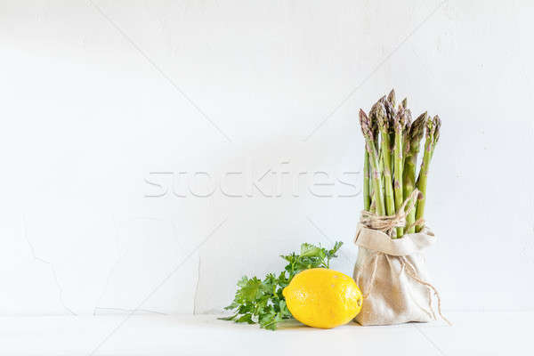 Stock photo: Bunches of fresh asparagus in a little sack, lemon and fresh par
