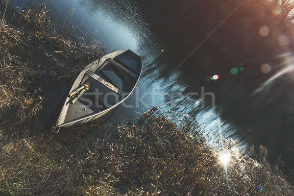 Wooden boat peacefully resting on the water of autumn river at t Stock photo © artsvitlyna