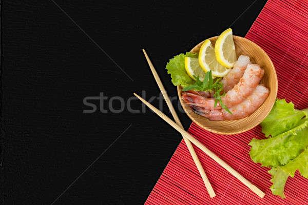 Shrimp on a wooden plate with wooden chopsticks Stock photo © artsvitlyna