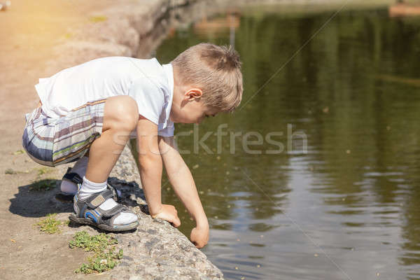 Stock photo: Happy little boy playing with water at the pond in the city park