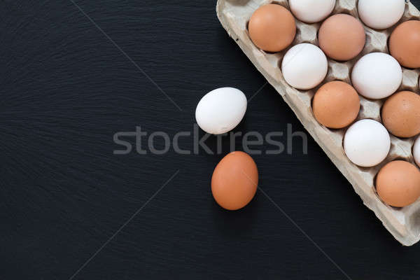 White and brown chicken eggs on black background Stock photo © artsvitlyna