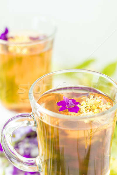 Stock photo: Linden herbal tea in a transparent grog glass with a linden blos
