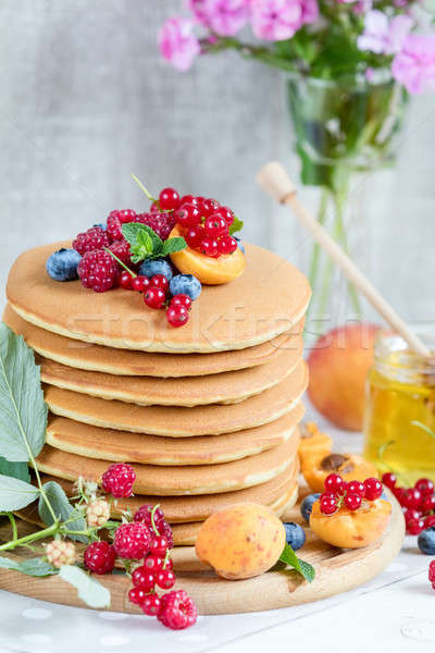 Fresh delicious pancakes with summer berries on light background Stock photo © artsvitlyna