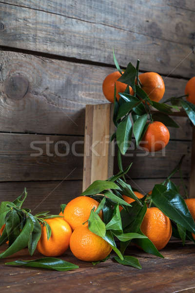 Tangerines with leaves on wooden box  Stock photo © artsvitlyna