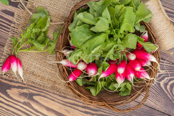 Bunch of radishes in a wicker basket on the table Stock photo © artsvitlyna