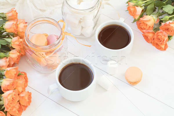 Orange macaroons, cup of coffee and fresh roses Stock photo © artsvitlyna