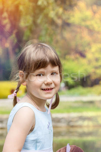 Stock photo: Cute little girl plaing in the city park on a summer sunny day.