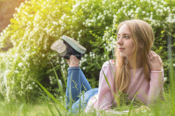 Cute blonde teenage-girl dreaming on a sunny day on the grass Stock photo © artsvitlyna