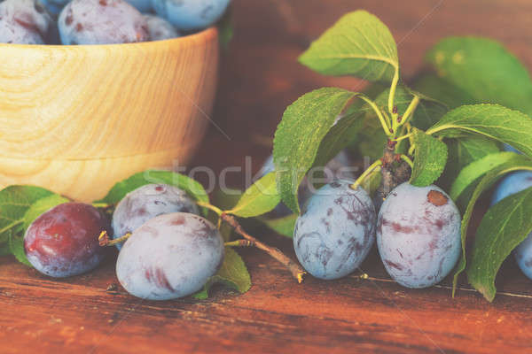 Fresh plums with green leaves in wooden pot on the dark wooden t Stock photo © artsvitlyna