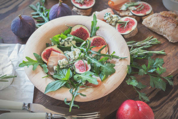Easy diet salad with arugula, figs and blue cheese on a brown wo Stock photo © artsvitlyna