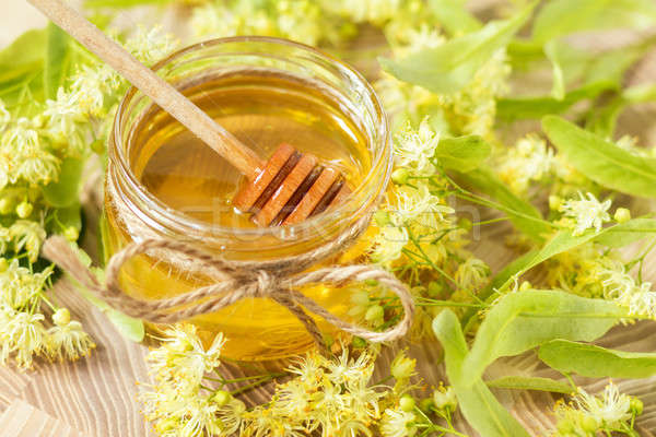 Honey in glass jars with white linden flowers Stock photo © artsvitlyna
