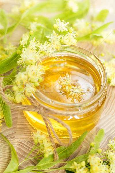 Stock photo: Honey in glass jars with white linden flowers