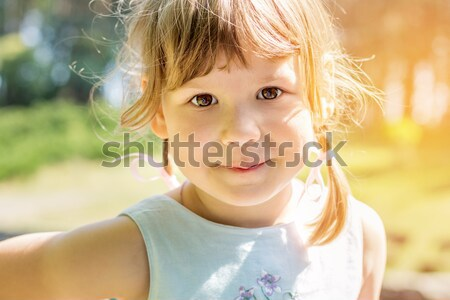 Cute little girl plaing in the city park on a summer sunny day.  Stock photo © artsvitlyna
