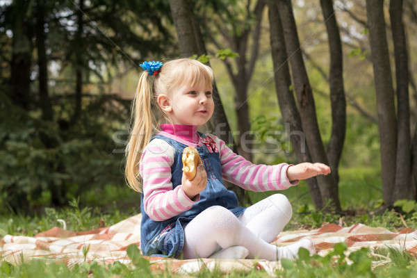 Stock photo: Cute little blonde girl with two ponytails relaxing with a book
