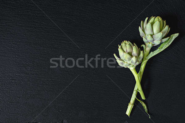Stock photo: Two cones fresh green artichoke on a black stone surface.  Top v