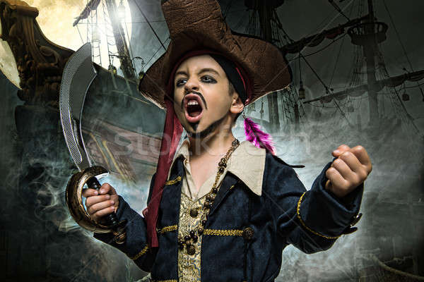 A angry young boy wearing a pirate costume. He stands on the background of the ship Stock photo © arturkurjan