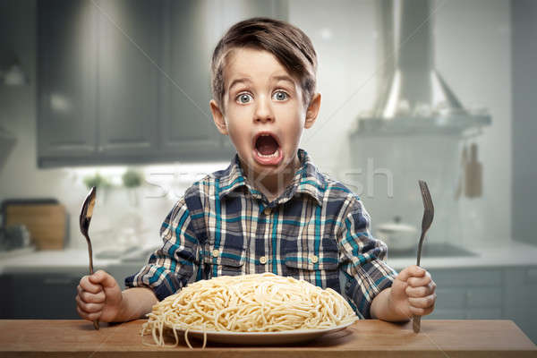 Startled yound boy with noodles Stock photo © arturkurjan