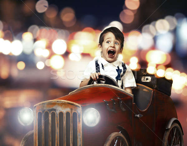 Smile child in wooden car in night on street Stock photo © arturkurjan