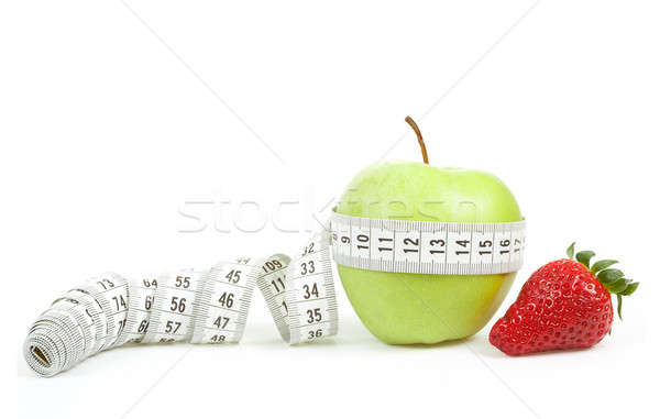 Stock photo: Measuring tape wrapped around a green apple and strawberry as a symbol of diet