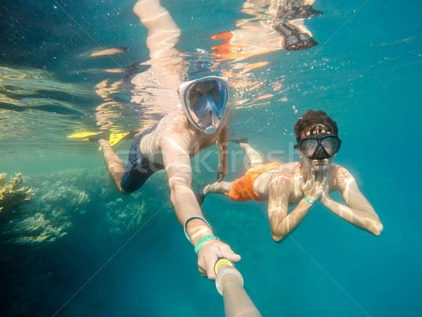 father and son snorkel in shallow water on coral fish Stock photo © artush