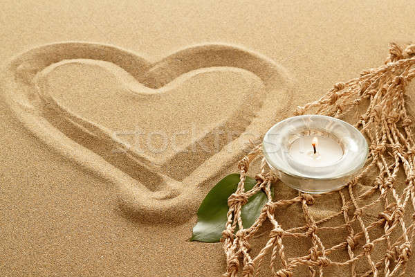 handwritten heart on sand with lighted candles Stock photo © artush