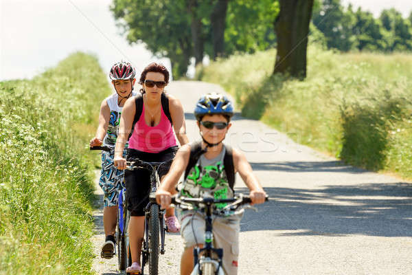 Mother with two sons on bicycle trip Stock photo © artush
