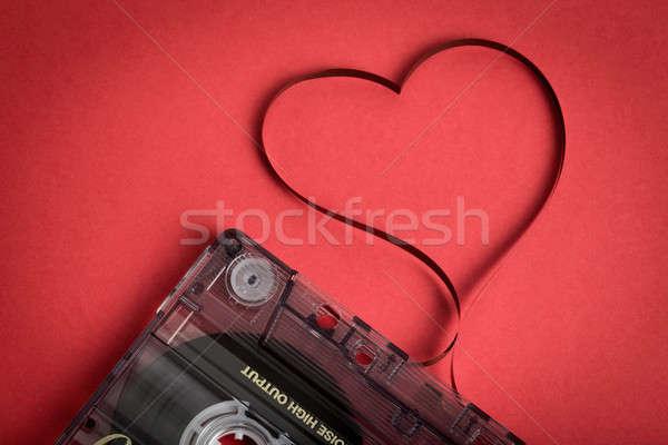 Audio cassette tape on red backgound. Film shaping heart Stock photo © artush
