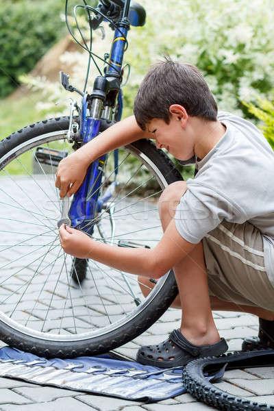 Teenager repairing his bike, changing broken tyre Stock photo © artush