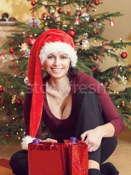 Beautiful middle age woman in santa hat sitting near the Christmas tree Stock photo © artush