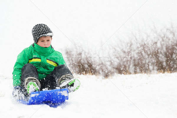 A young boy shows his excitement sledding down a hill in winter Stock photo © artush