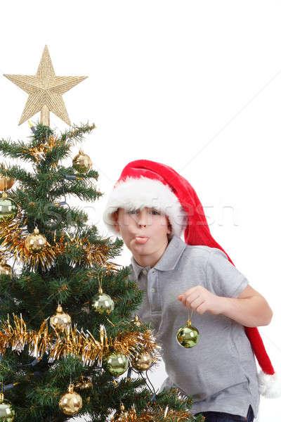 Boy with santa hat sticking out tongue at  the Christmas tree Stock photo © artush