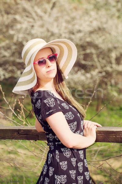 Cheerful fashionable woman in stylish hat, frock and sunglasses Stock photo © artush