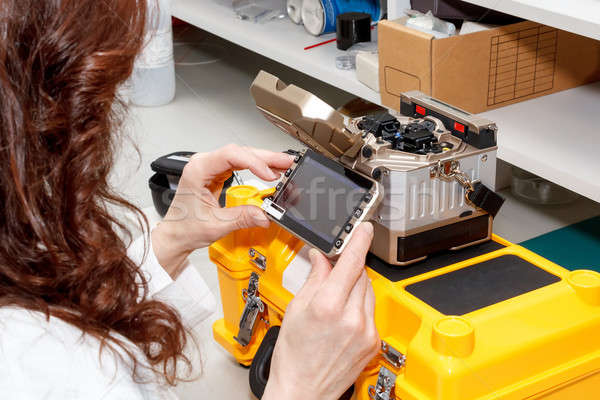 woman working with fiber optic fusion splicer Stock photo © artush
