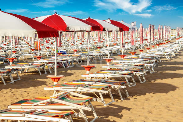 red and white umbrellas and sunlongers on the sandy beach Stock photo © artush
