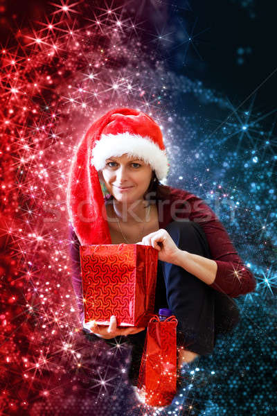 Beautiful middle age woman in red party santa hat sitting with gifts, with abstract background Stock photo © artush