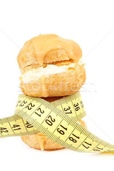 concept of slimming, caramel cakes with measuring tape Stock photo © artush