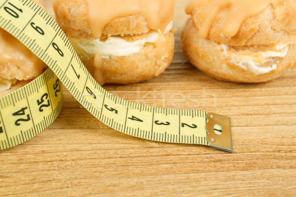 concept of slimming, closeup of caramel cakes with measuring tape Stock photo © artush