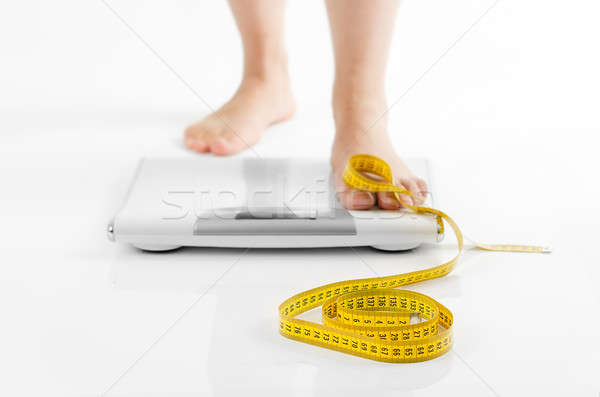 A picture of female feet standing on a bathroom scales and a tap Stock photo © ashumskiy