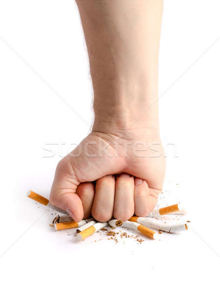 Stock photo: Man's fist crushing cigarettes
